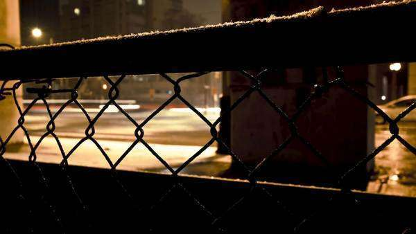 Motion timelapse of a fense with cars going by in the background during a cold and wet evening Royalty-free stock video