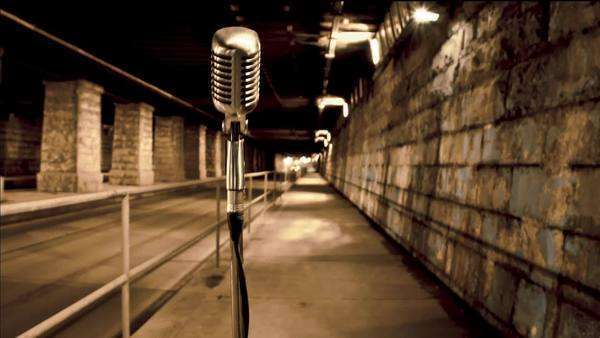 Motion timelapse of a microphone standing in tunnel under a bridge as cars and pedestrians go by Royalty-free stock video