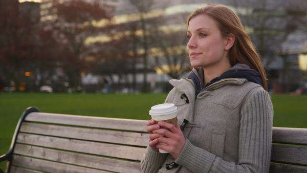 Young woman sits on park bench with cup of coffee Royalty-free stock video