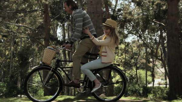 Couple riding one bicycle through forest Royalty-free stock video
