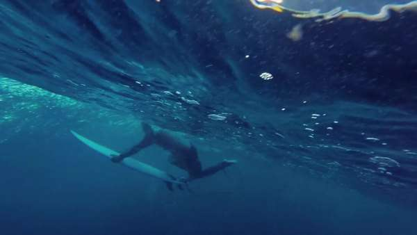Profile of man swimming underwater with surfboard. Royalty-free stock video