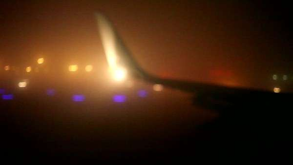 Tail of airplane as it gains speed for takeoff on runway at night Royalty-free stock video
