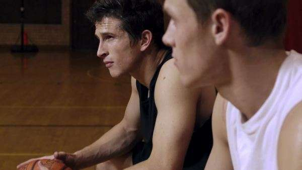 8b68a9bbe9d2 Slow motion shot of two sweating young men sitting  one bounces a  basketball.