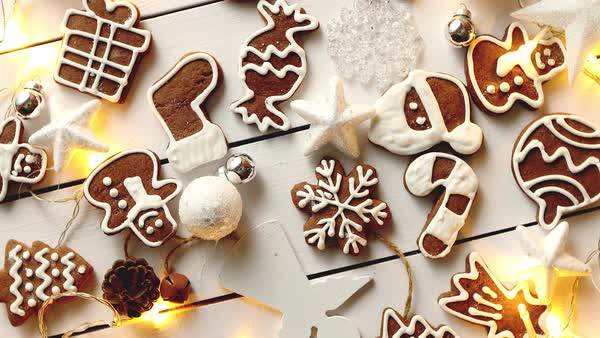 Christmas Sweets.Christmas Sweets Composition Gingerbread Various Shaped Cookies With Xmas Decorations Arranged On White Wooden Table With Lights Stock Footage