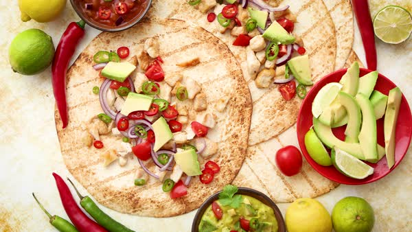 Freshly made healthy corn tortillas with grilled chicken fillet, big  avocado slices, fresh salsa, limes and differend sides  Placed on rusty  table