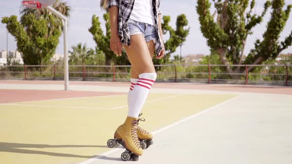 b086bb025b5 Cute single woman in flannel shirt and cut jeans shorts using the toe  brakes on her roller skates at basketball court surrounded by tropical  trees - Stock ...