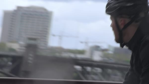Tilt shot of commuter riding bicycle on bridge in city Royalty-free stock video
