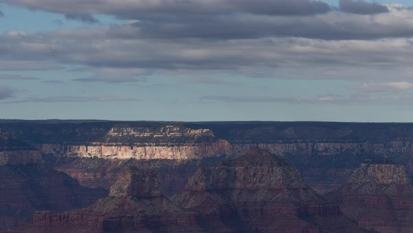 Long-lens shot of the far-rim of the Grand Canyon as clouds roll overhead before a rainstorm. Royalty-free stock video