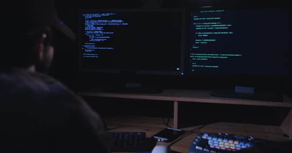 Computer Hacker sitting in a dark room in front of screens and writing  lines of code stock footage