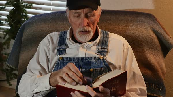 Old Man Wearing Coveralls Tries To Read Book Without Reading D1091 7 004