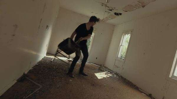 Handheld shot of a man throwing a chair against a wall in a crumbling room Royalty-free stock video