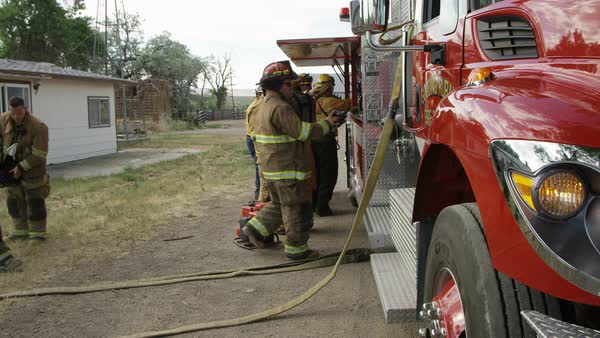 Firemen next to fire truck getting gear on for training Royalty-free stock video