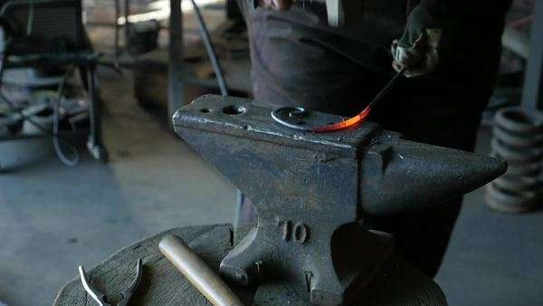 Medium shot of a blacksmith hammering wrought iron Royalty-free stock video