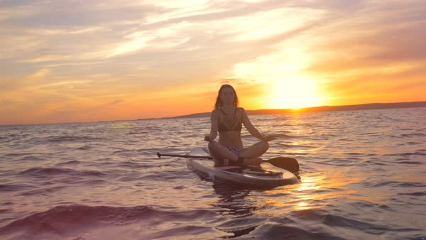 Gorgeous Woman Is Sitting In A Lotus Pose On A Board During Sunset Practicing Yoga Stock Footage