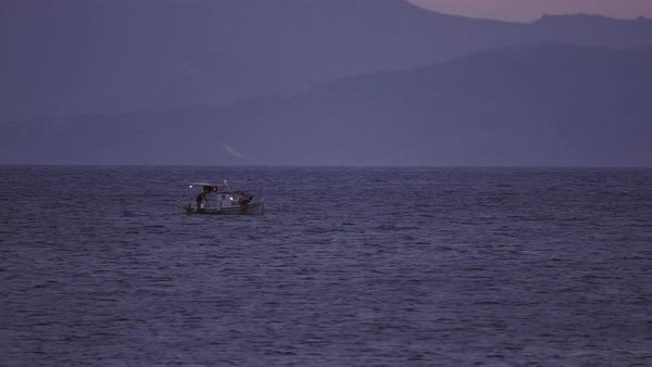 Fisherman on fishing boat at dusk far in the open sea Royalty-free stock video