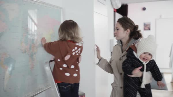 Medium shot of a woman teaching her child in front of a world map Royalty-free stock video