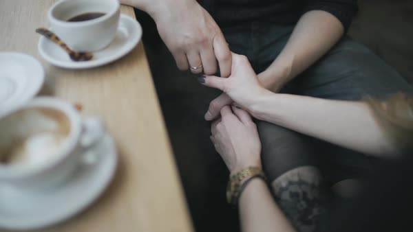 Hand-held shot of a couple holding hands in a coffee shop Royalty-free stock video