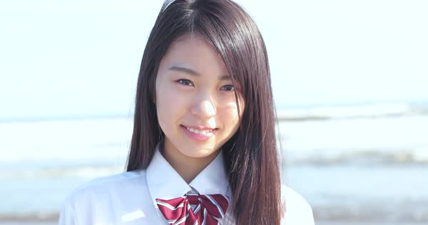 Japanese Girl In School Uniform Smiling At The Camera On