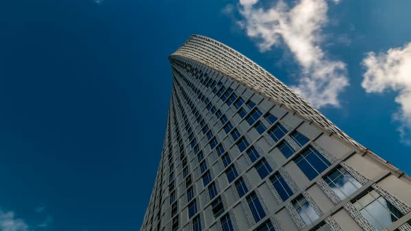 Cayan Tower timelapse (known also as Infinity Tower) in Dubai Marina   Perspective view from bottom to cloudy blue sky, The tower is world's  tallest