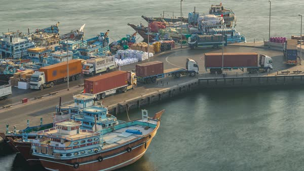 Loading a ship in Port Said timelapse in Dubai, Deira creek, UAE  Aerial  top view from above with many old boats at sunset with warm light stock
