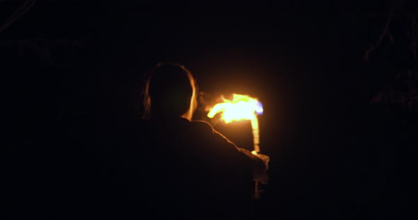 Medium shot of a woman holding a torch at night Royalty-free stock video