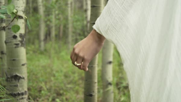 Close-up tracking shot of a woman walking in a forest Royalty-free stock video