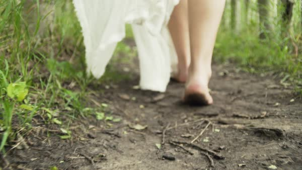 Close-up tracking shot of a barefoot woman walking Royalty-free stock video