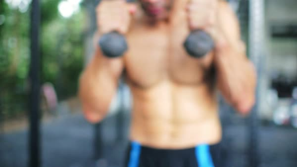 Sport man boxing with dumbbells during warm up before bodybuilding training  stock footage