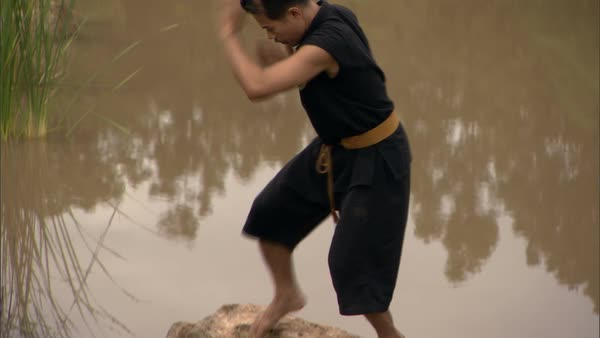 Tilt-up shot of a man practicing martial art positions at a riverside Rights-managed stock video