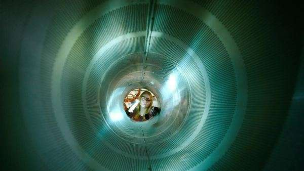 Push-in shot of a female engineer inspecting inside of metal cylinder. Originally sourced from 70mm film Rights-managed stock video