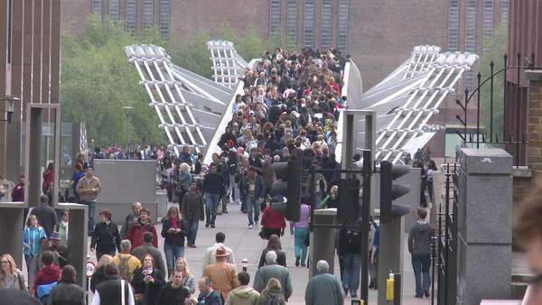 Hand-held shot of crowded Millennium Bridge in London Rights-managed stock video