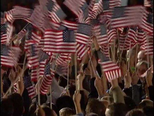 Panning shot of a crowd waving American flags Rights-managed stock video