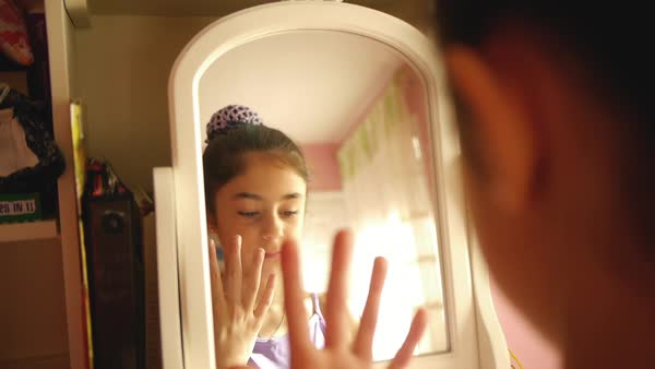 Hand-held shot of a girl putting on jewelry in front of a mirror Royalty-free stock video