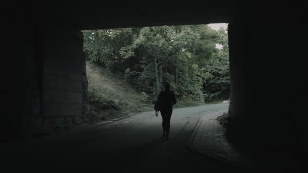 Tracking shot of a woman walking out of an underpass Royalty-free stock video