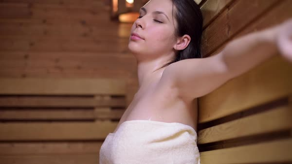 Beautiful woman sitting and relaxing in sauna cabin dolly shot Royalty-free stock video
