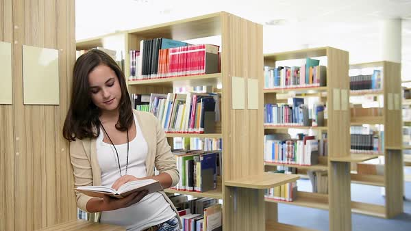 Standing young female student reads book in college library Royalty-free stock video
