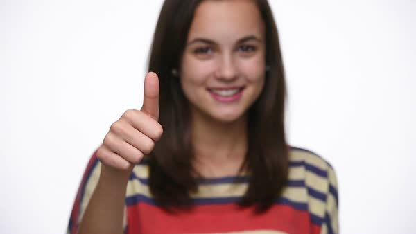 Rack focus of teenager girl showing thumbs up isolated on white studio shot Royalty-free stock video