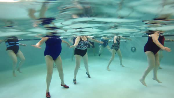 Underwater scene featuring group of elderly women exercising during an aquatics health wellness class in a swimming pool. Royalty-free stock video