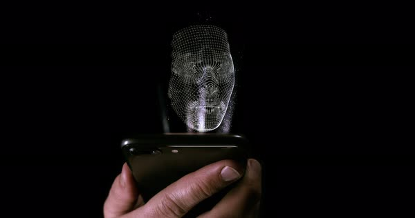Male holding up a smart phone with a facial hologram projecting out of the  screen stock footage