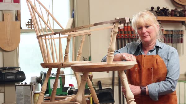 Female Furniture Maker Making A Windsor Chair In Workshop Stock