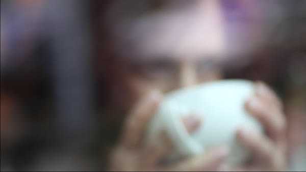 Hand-held shot of a woman drinking a cup of coffee Royalty-free stock video