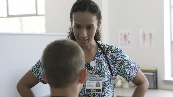 Hand held shot of a doctor working greeting a child Royalty-free stock video