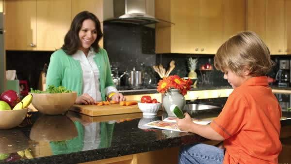 Mother preparing food in kitchen while son does homework Royalty-free stock video