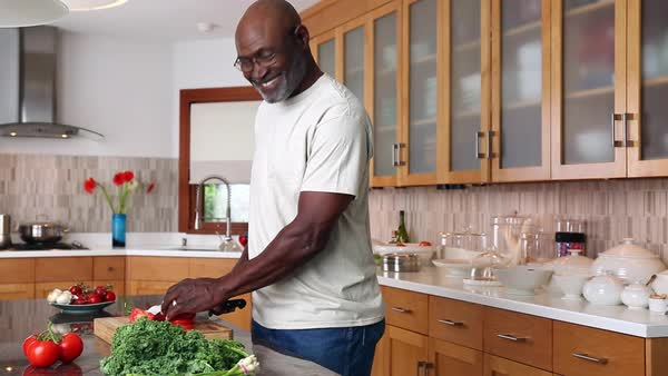 Woman kissing smiling African American man chopping tomato in domestic kitchen Royalty-free stock video