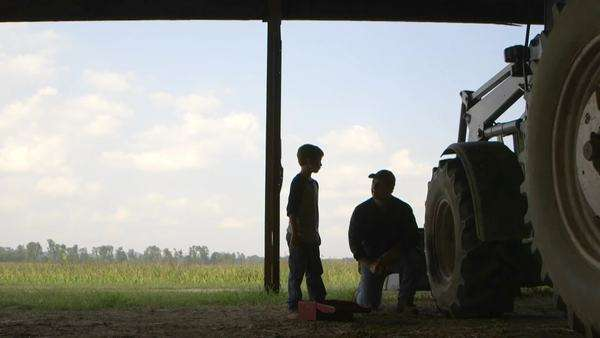 Caucasian father explaining tractor repair to son Royalty-free stock video