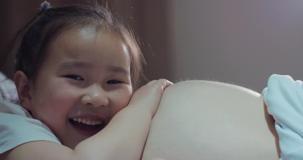 Close up of one lovely little Chinese girl lying on her pregnant mother's  belly at evening in the bedroom, happy child talking to pregnant mother at
