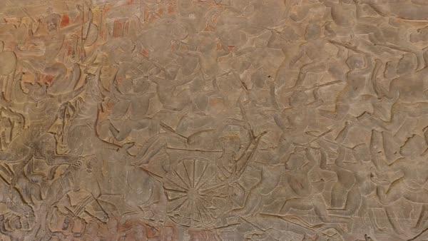 Pan across bas relief carvings of temple wall at angkor wat