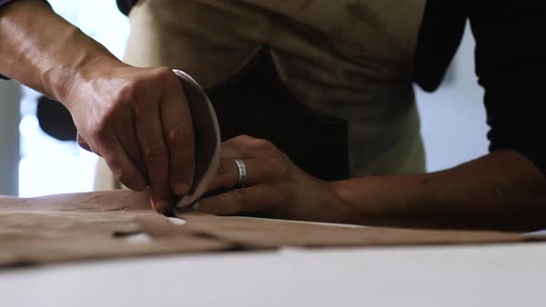 Close-up shot of a craftsman cutting a leather Royalty-free stock video