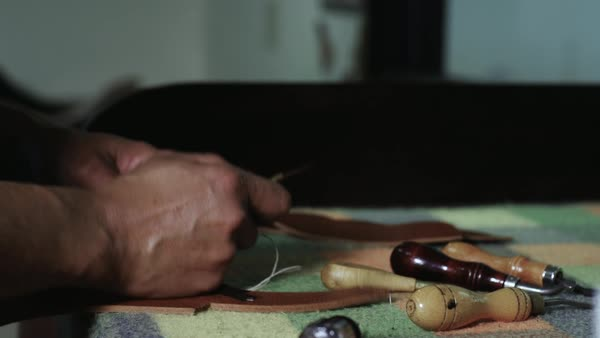 Close-up shot of a craftsman sewing a piece of leather Royalty-free stock video