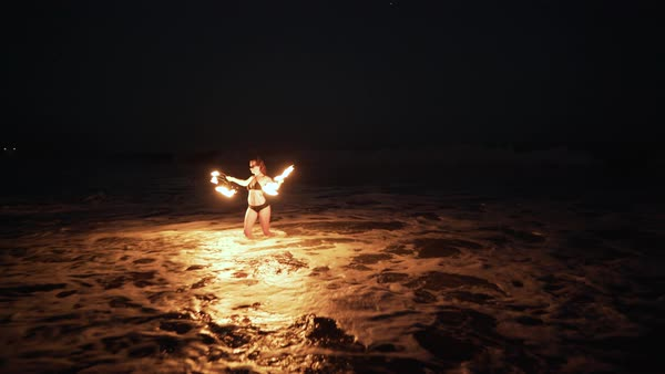 Gimbal shot of a fire dancer performing with fire fans on a beach Royalty-free stock video